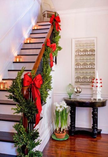 Drape a green garland up the handrail of a staircase, and add gold bows in between for a Christmas welcome in your living room.